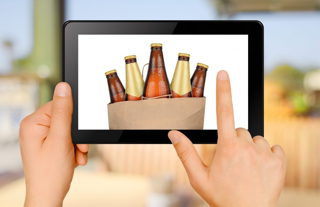 Two hands looking at cold beers on a computer tablet
